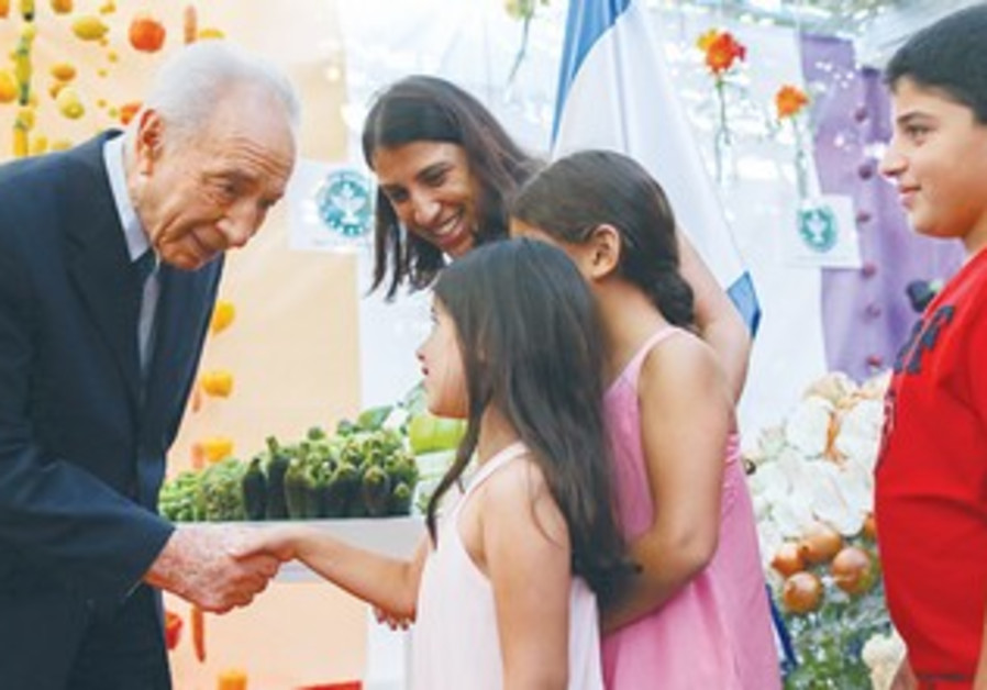 PRESIDENT SHIMON PERES greets young children in his succa at the President's Residence in Jerusalem.