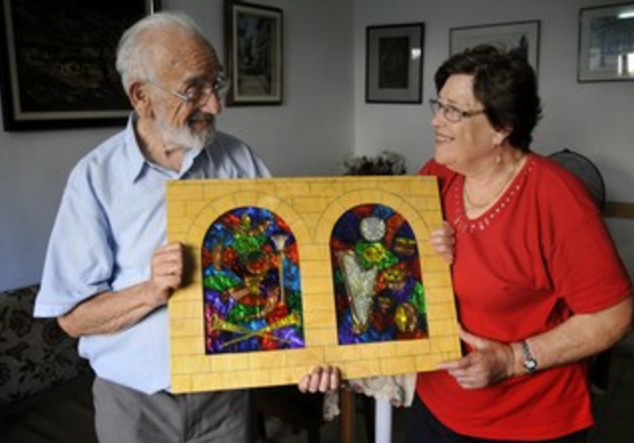Meir and Miriam Parush hold a stained glass images from the Sukkah, at their home in Givatayim.