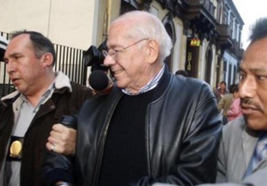 Israeli former judge Dan Cohen is escorted by police.