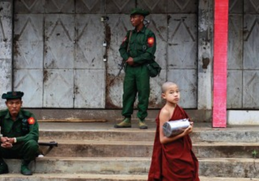 Buddhist monks walk past soldiers in the town of Lashio in Myanmar.