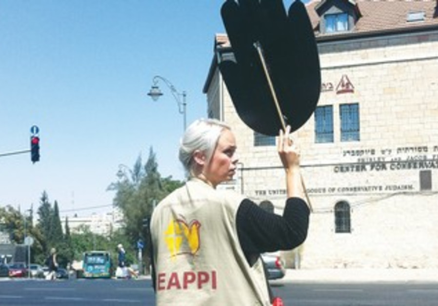A protester from the World Council of Churches demonstrates with Women in Black in Jerusalem.