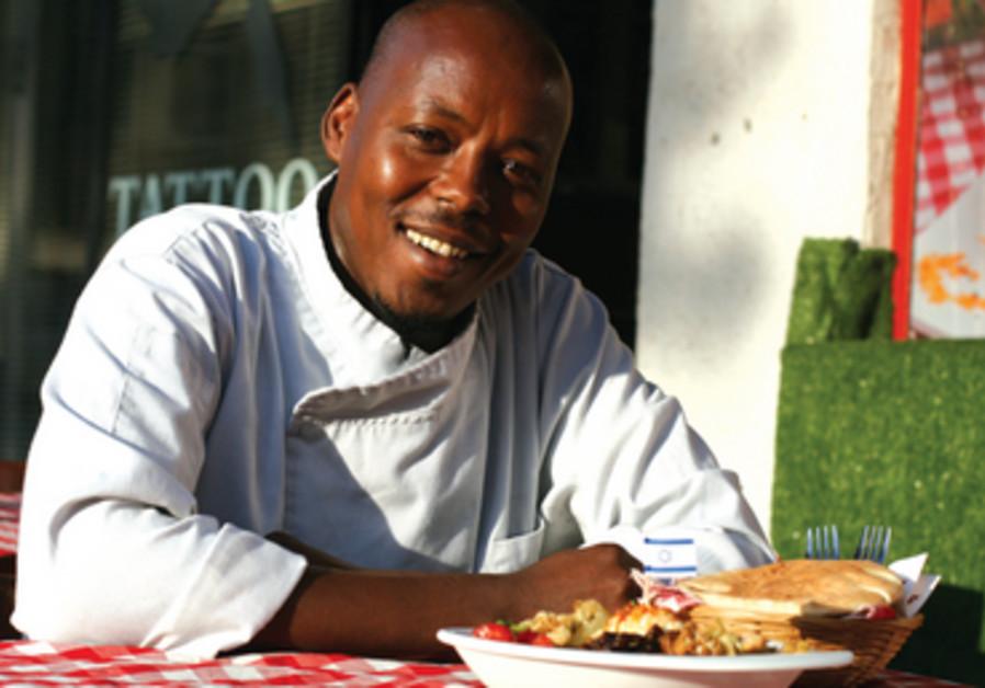 Seifallah Bush dans son restaurant Shakshoukan. Devant lui, son assiette de houmous complète