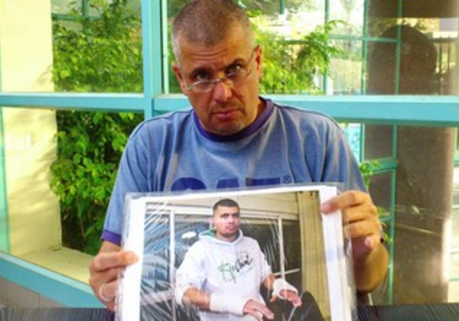 Rafi Rotem showing a picture of himself after he says he was beaten by police in custody.