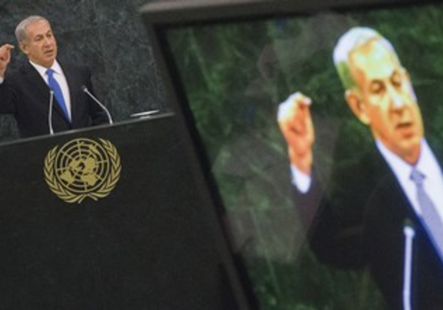 BINYAMIN NETANYAU is pictured on a television monitor while addressing the 68th session of the UNGA