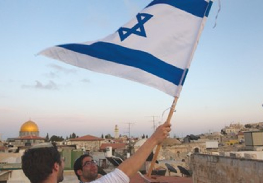 A JEWISH man waves a flag with the Temple Mount in the background.