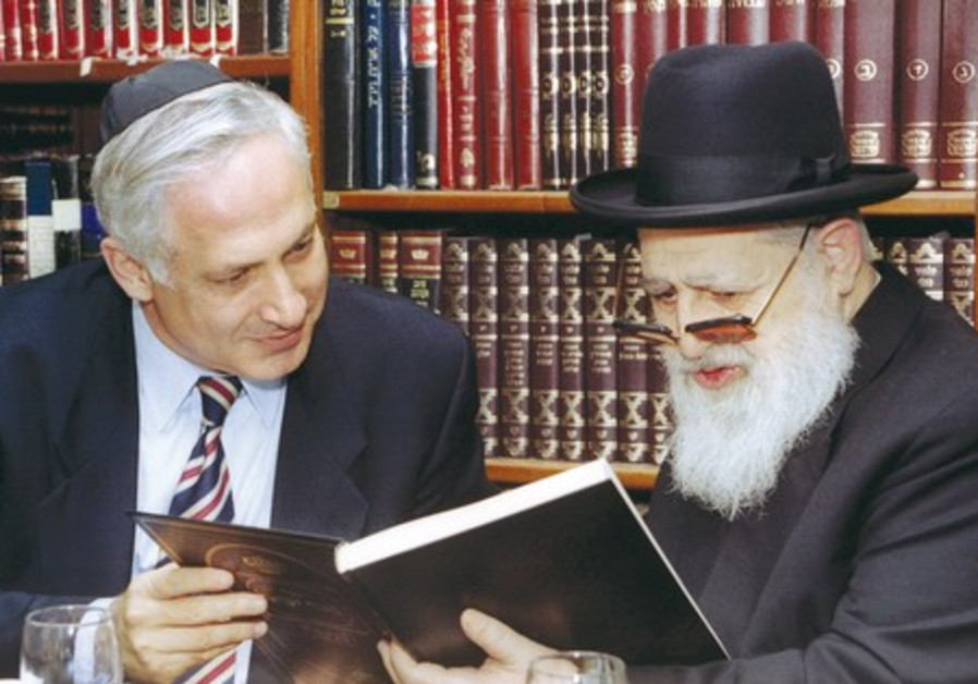 RABBI OVADIA Yosef reads the dedication of a book he gave to Prime Minister Binyamin Netanyahu.
