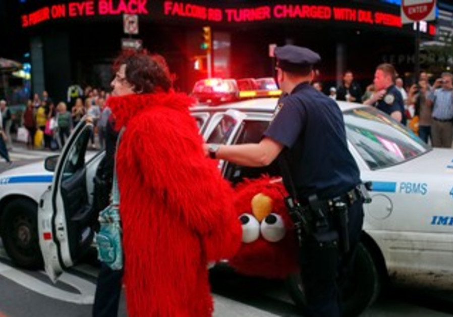 Dan Sandler, dressed as Elmo, is handcuffed and detained, September 18, 2012