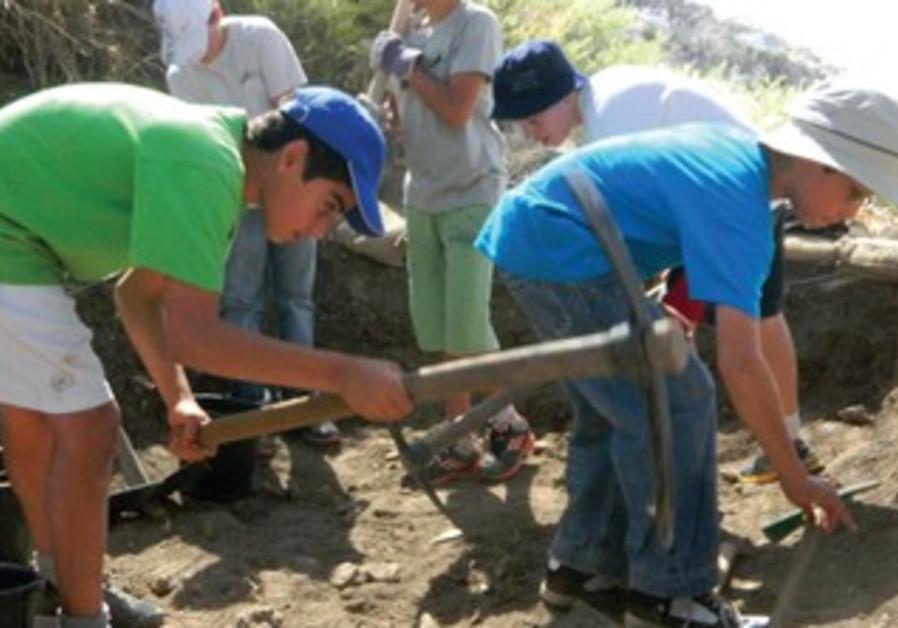 ROEE NETZER, 13 (left), wields a pick axe alongside his classmates at the Tel Esur site.