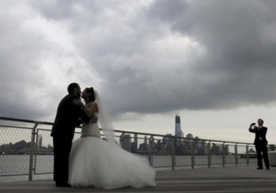 Bride and groom pose under rain clouds [illustrative]