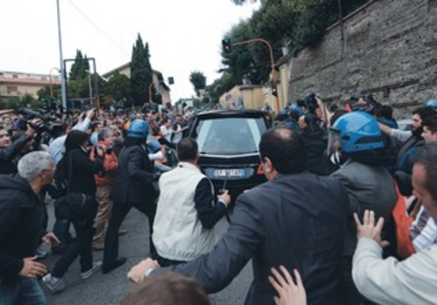 ANTI-FASCIST demonstrators shout as the hearse carrying Nazi war criminal Priebke passes near Rome