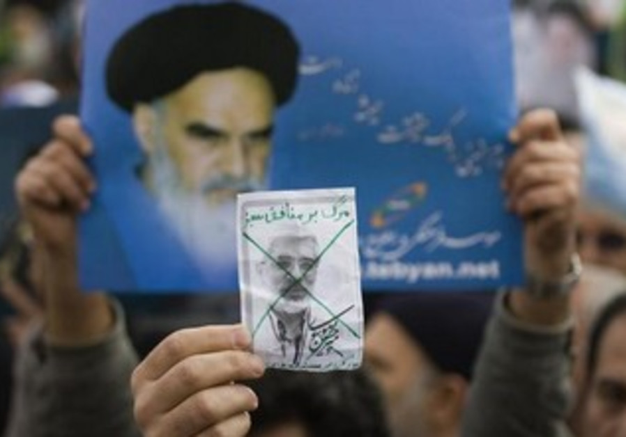 A worshiper holds a picture of opposition leader Mirhossein Mousavi.