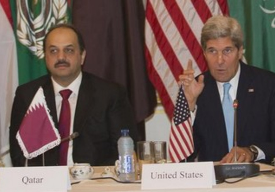 Qatari Foreign Minister Khalid Bin al Attiyah (L) and U.S. Secretary of State John Kerry