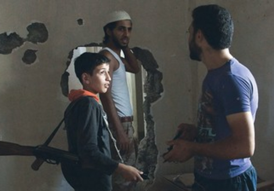 A 14-year-old fighter with the Free Syrian Army chats with his fellow fighters in Deir al-Zor.