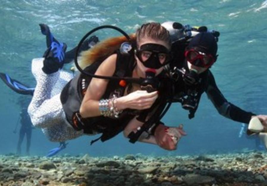 Assistant escorts a model in underwater shoot in Eilat