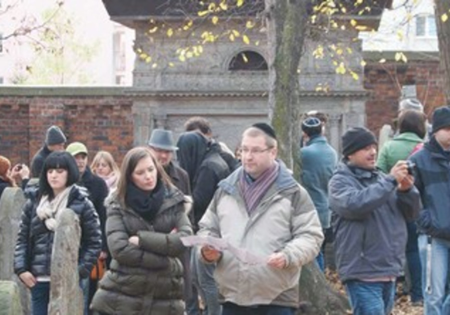RUSSO-GERMAN JEWS walk in the Warsaw Jewish cemetery.