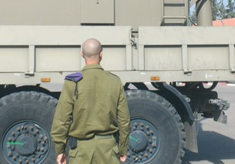 LT.-COL. OMER (last name withheld) stands near an advanced Amirim Battalion communications truck.