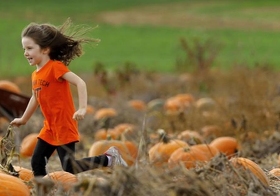 Olivia Thomas runs through pumpkin field