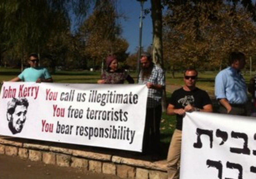 DEMONTSRTERS POSE behind banners Sunday morning