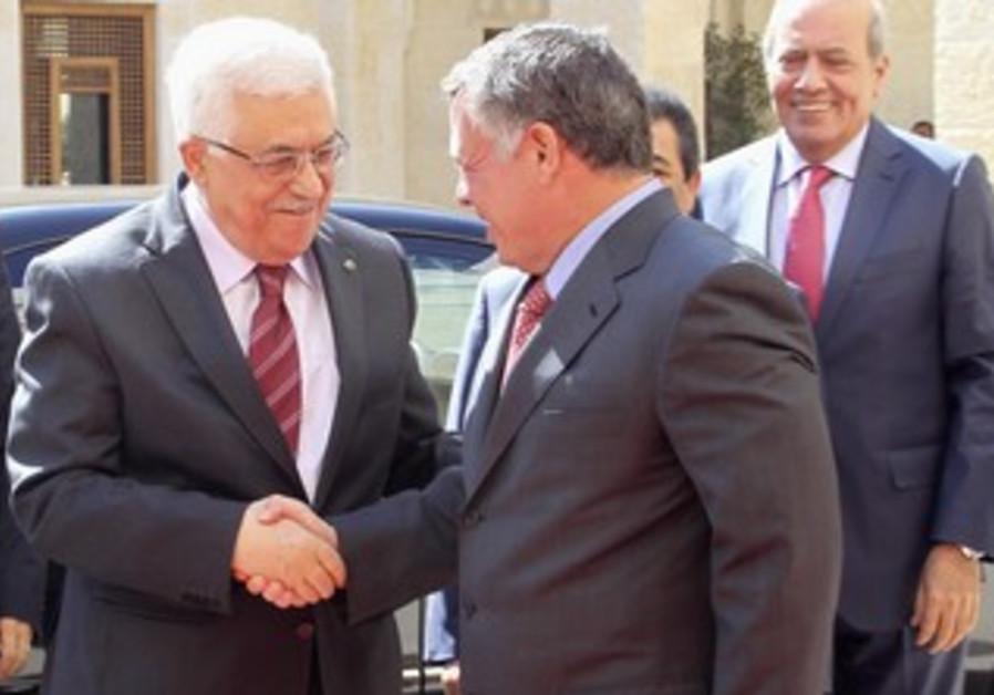 Jordan's King Abdullah welcomes PA President Mahmoud Abbas at the Royal Palace in Amman