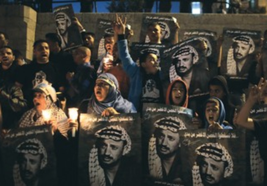 Palestinians hold posters of the late Yasser Arafat during a rally in Jerusalem.