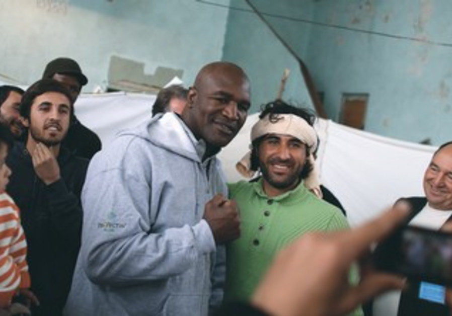 Retired boxer Evander Holyfield with Syrian refugees during visit to camp in Sofia, Bulgaria.