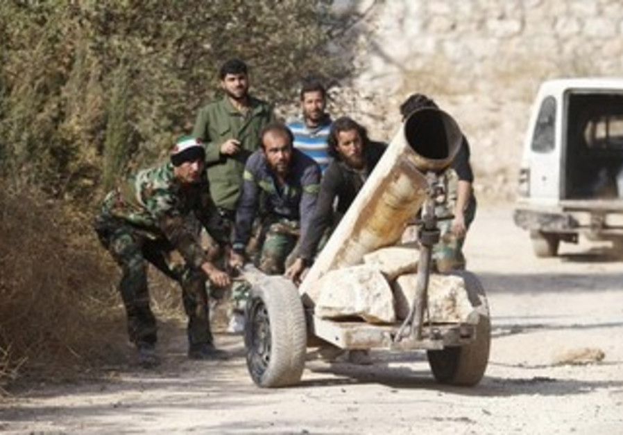 Syrian opposition fighters drag a rocket launcher near the 80th Brigade base in Aleppo Nov. 13, 2013