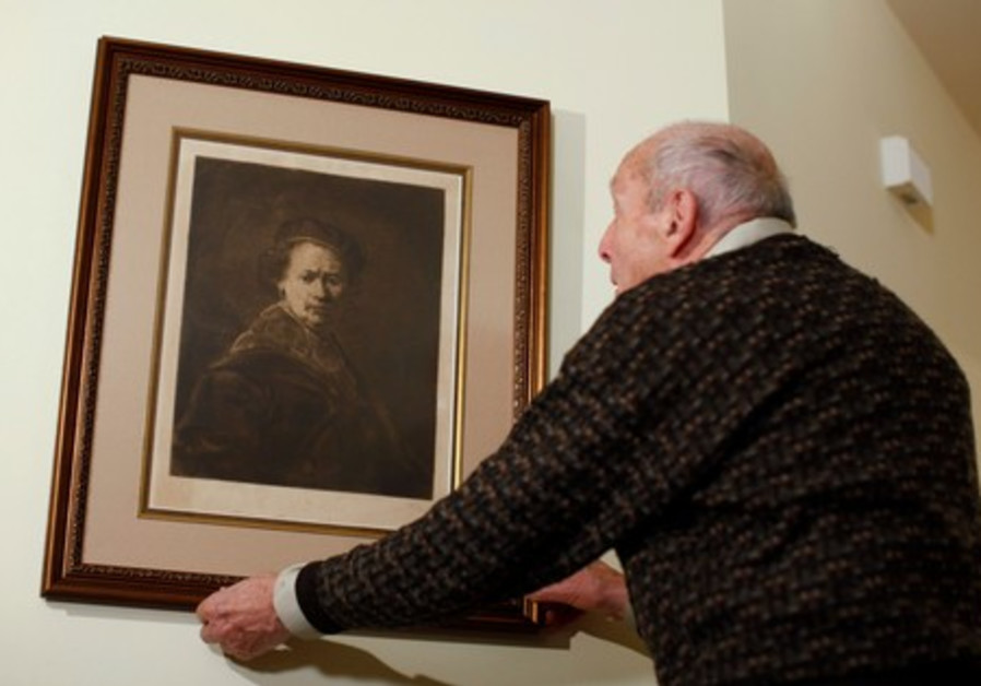 Harry Ettlinger adjusts his print of a Rembrandt self-portrait at his home at Rockaway in New Jersey