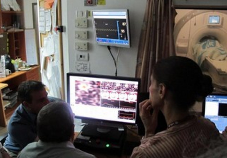 A patient (through window) undergoing non-invasive ablation for essential tremor.