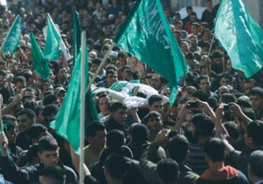 A crowd waves Hamas flags during an Islamist's funeral