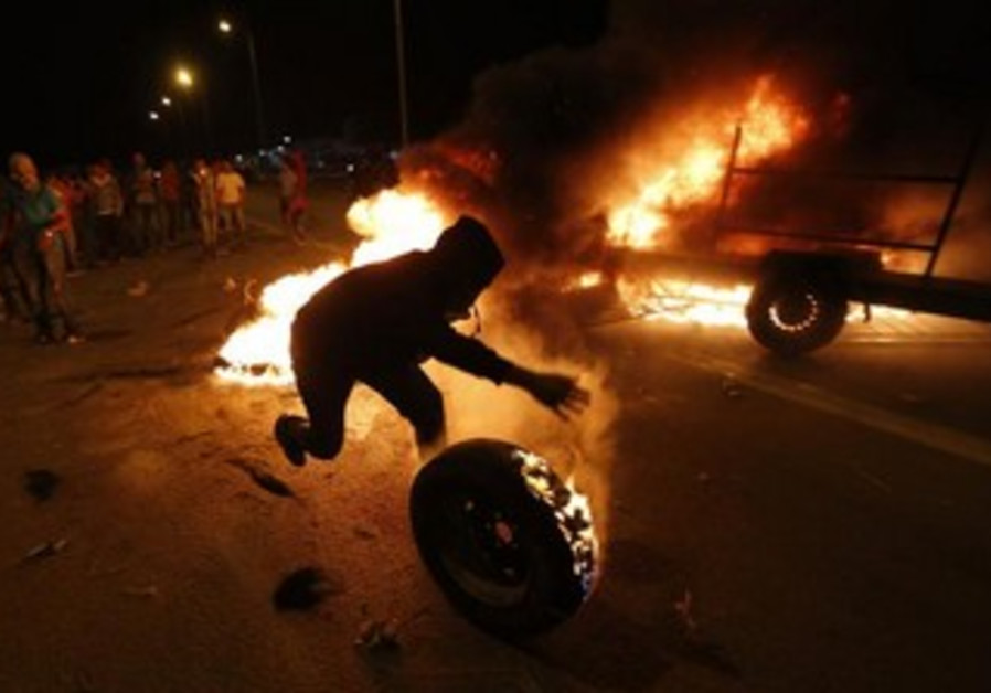 A protester rolls a burning tire towards police during a demonstration against the Prawer plan.