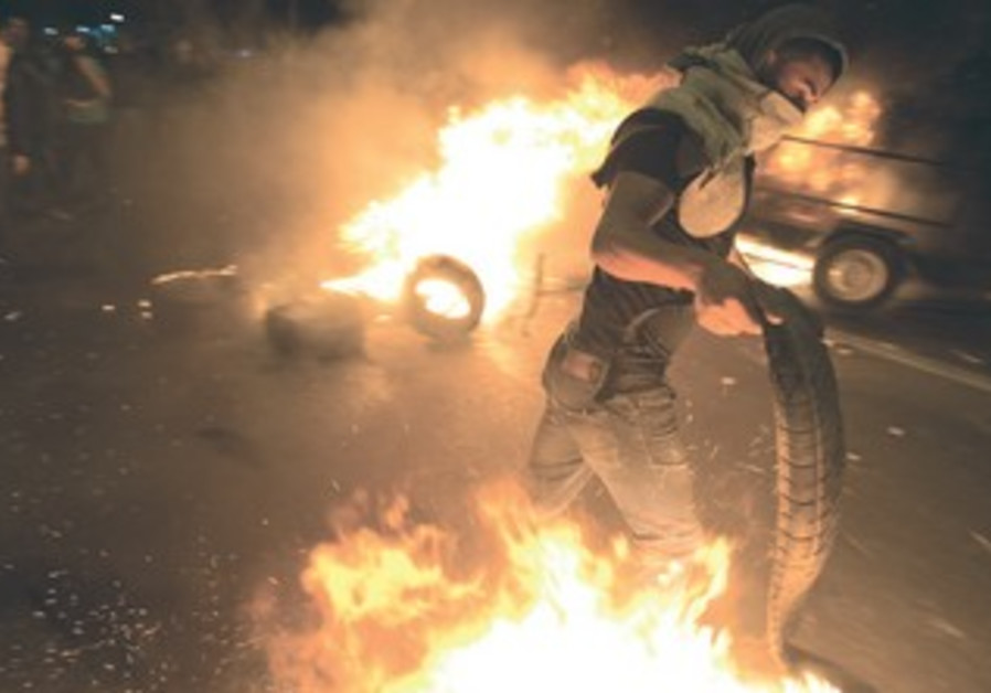 A BEDUIN PROTESTER carries a burning tire during clashes with police in the southern village of Hura
