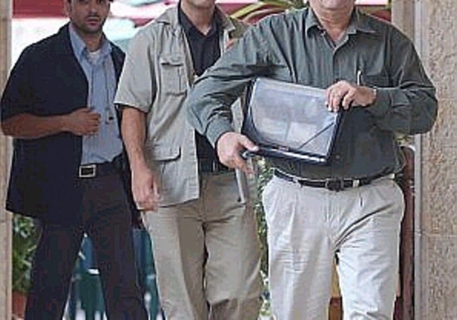 yonatan bassi walking with guards holding folder 2