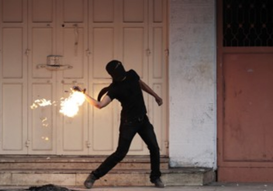 Palestinian throws Molotov cocktail during clashes with IDF after funerals of 3 Palestinians, Nov 27