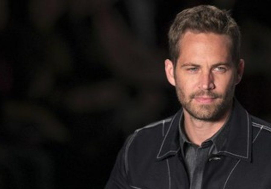 US actor Paul Walker presents a creation from Colcci's 2013/2014 summer collection in Sao Paulo