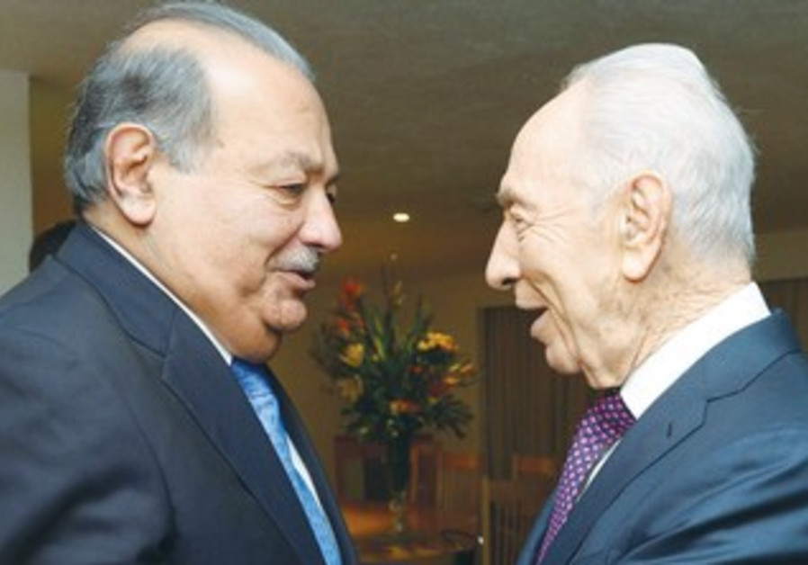 President Shimon Peres embraces Carlos Slim, reputed to be the world's wealthiest individual