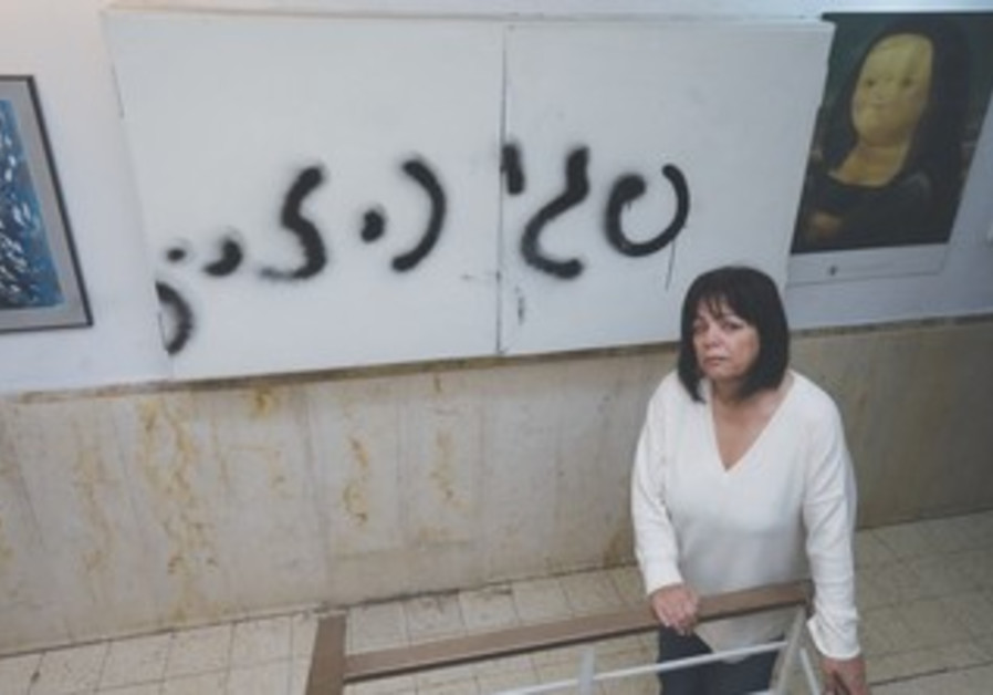 """Peggy Cidor standing in hallway of apartment where the words """"Peggy, watch out"""" were spray-painted."""