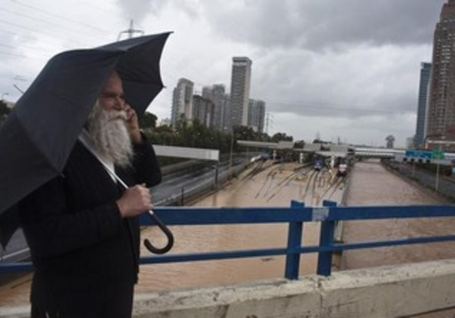 A man stands on a bridge overlooking flooded railway tracks