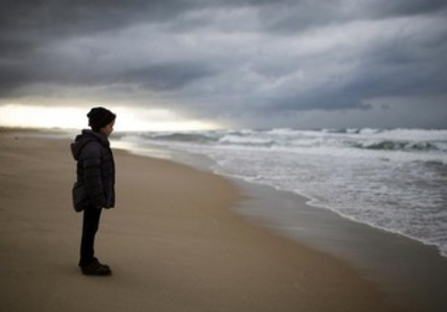 An Israeli girl stands on Zikim beach