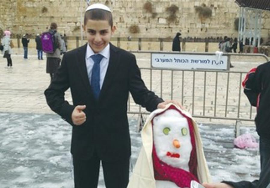 Bar mitzva boy poses with snow woman at Kotel