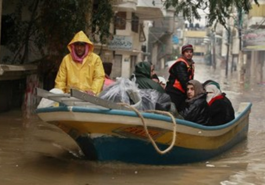 Palestinian civil defense members evacuate people from flooded houses in the northern Gaza Strip.