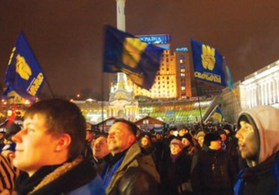 ANTI-GOVERNMENT protesters wave Svoboda flags at Maidan Square in Kiev, Dec. 11, 2013