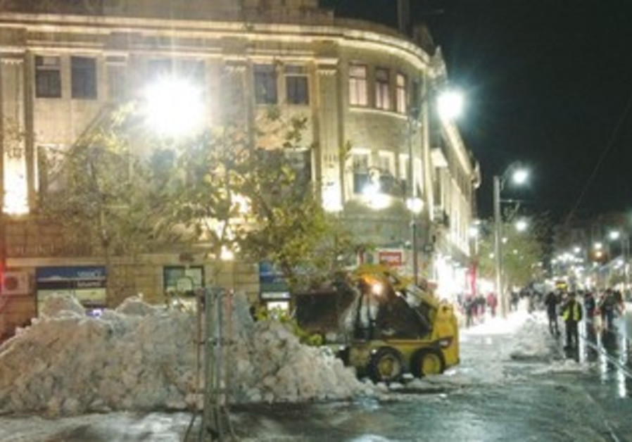 A plow truck clears road of snow in Jerusalem