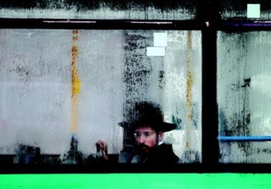 Jeune homme ultraorthodoxe assis seul à l'écart dans un bus public.