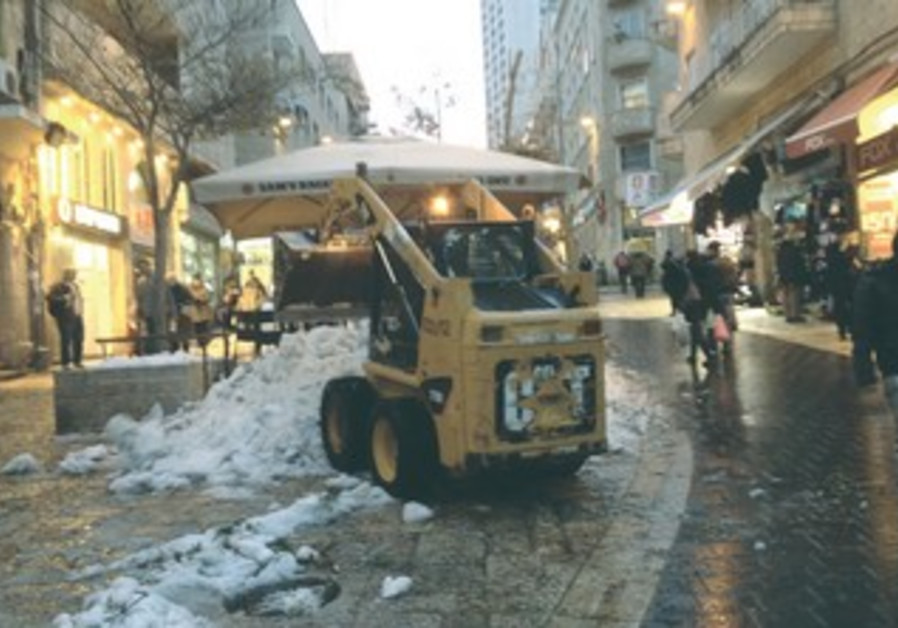 A plow collects snow remaining on Jerusalem's normally bustling Ben-Yehuda Street December 17, 2013