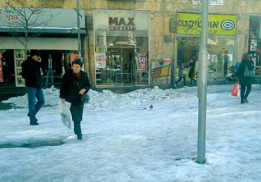 Snow remains on the ground at the intersection of Jerusalem's King George Avenue and Ben-Yehuda St.