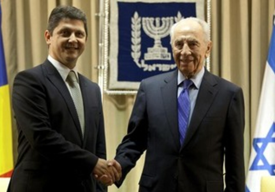 President Shimon Peres (R) shakes hands with Romania's Foreign Minister Titus Corlatean, Oct. 2012.
