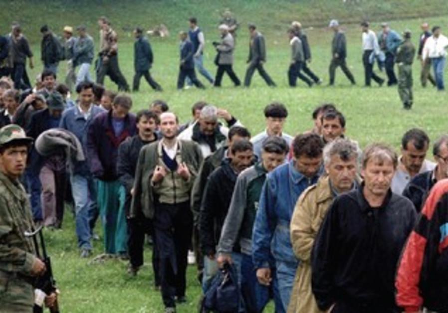 BOSNIAN CROAT soldiers taken as prisoners pass a Bosnian Serb soldier, 1993
