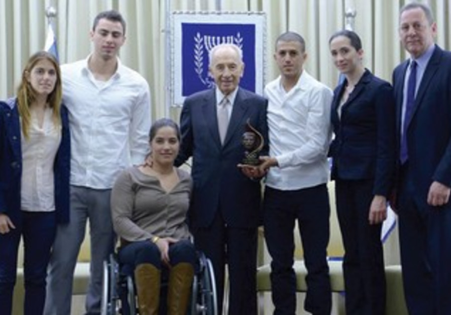 President Shimon Peres poses with a delegation of the Israel Olympic Committee.