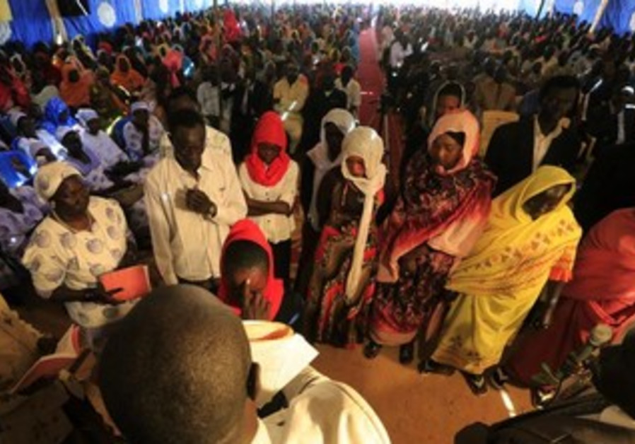 Members of the Nuba tribe from South Kordofan state receive blessings from a priest during Christmas