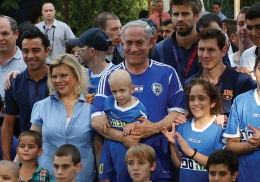 Netanyahu and his wife, Sara, pose with young cancer patients and soccer star from Barcelona